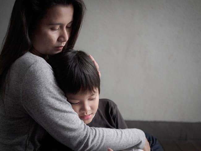 Mother holding grieving son