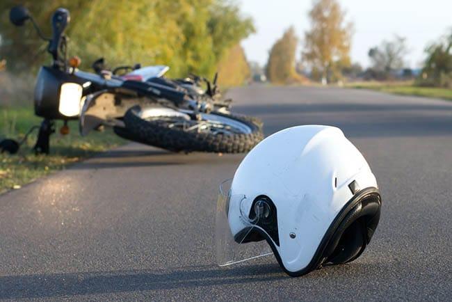 Motorbike and helmet on ground of street