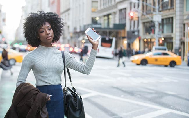 Woman flagging ride share vehicle down