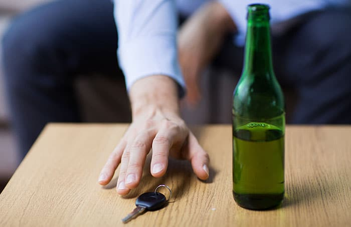Man reaching for car keys after drinking