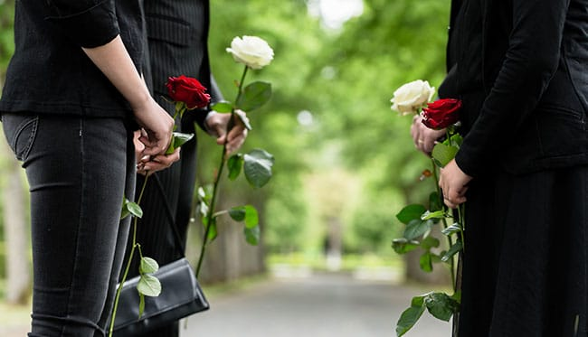Group of friends exchanging roses at funeral