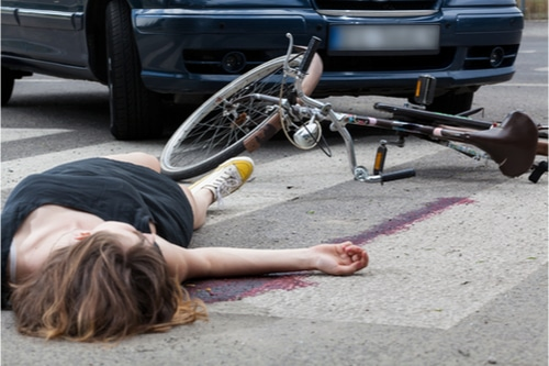 Woman lying next to her bike, car in the background