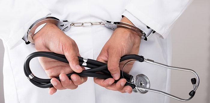 Doctor in handcuffs with stethoscope in hands