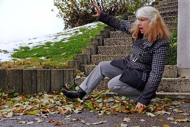 Woman slipping on pile of leaves at base of stairs