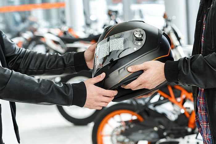 Motorcycle rider buying safety helmet