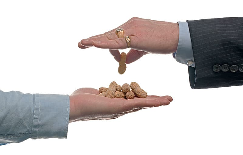 Boss handing employee peanuts for pay
